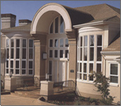 Picture of a front of a house with a lot of nicely designed windows.